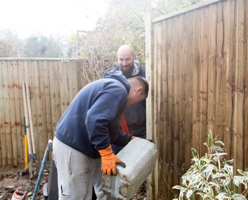 A photo of two men installing a new closeboard fence using postcrete