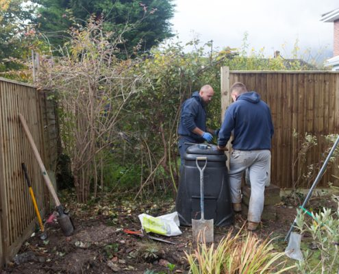 A photo of two men installing a new closeboard fence