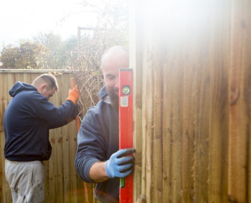 A photo of a two men installing a new fence