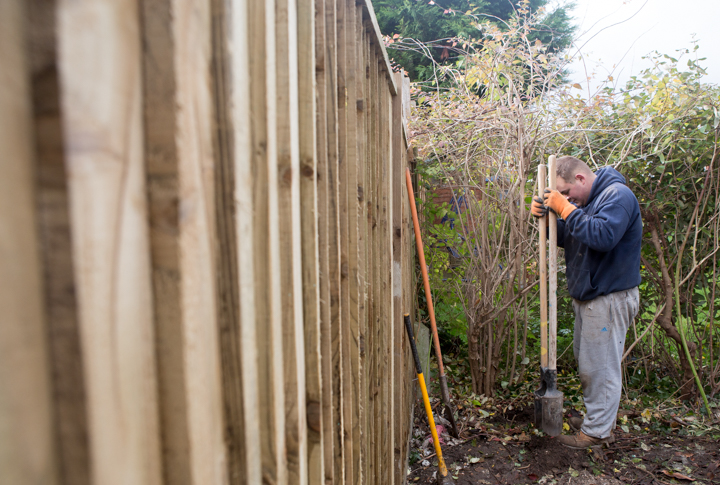 A photo of a man digging a hole for a fence post.