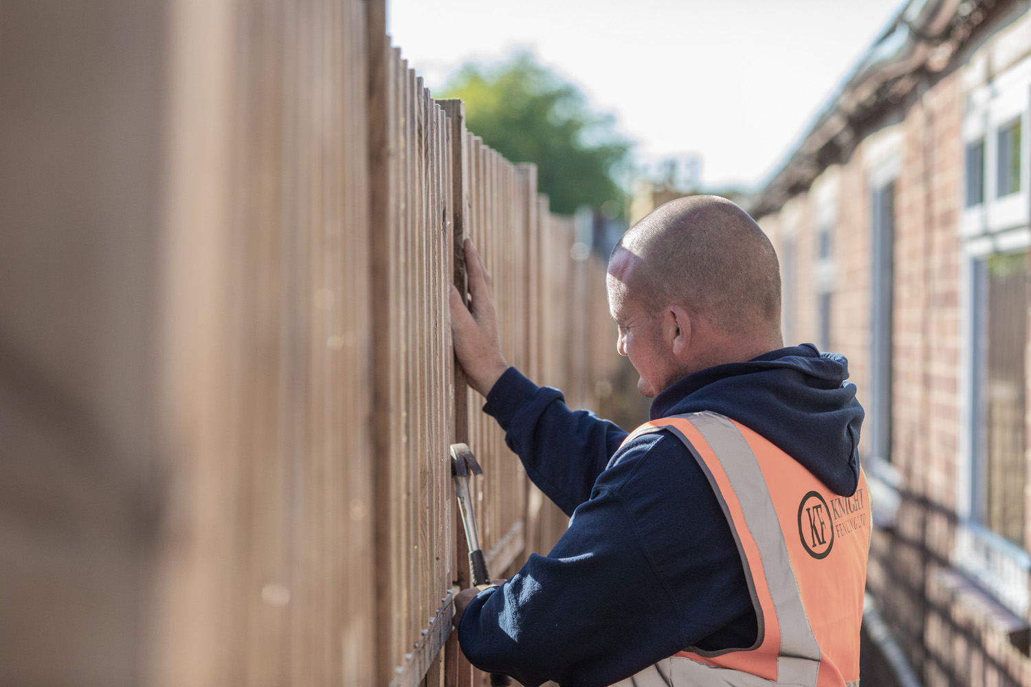 a man performing a fence installation