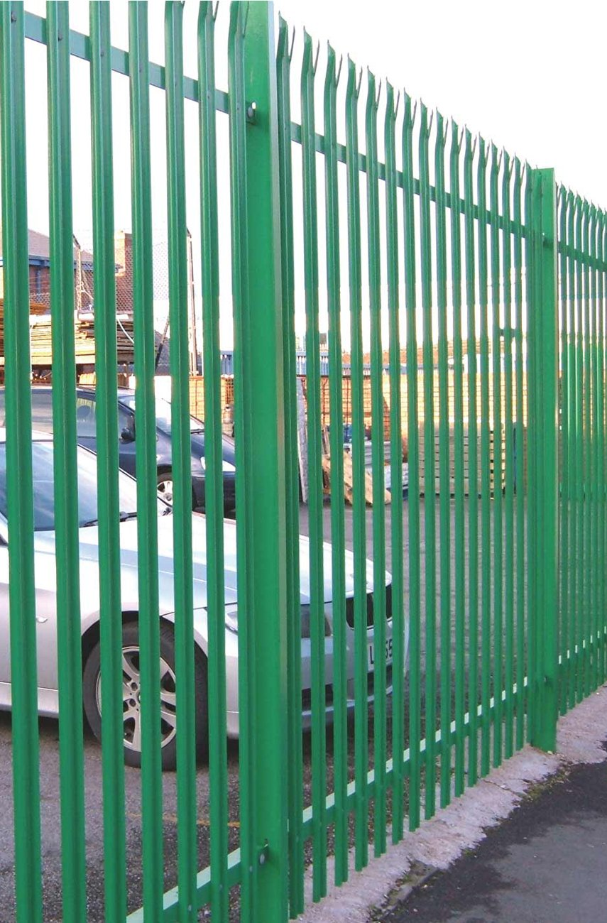 A photo of a green metal fence in an industrial setting
