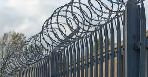 A photo of a metal fence with barbed wire on top