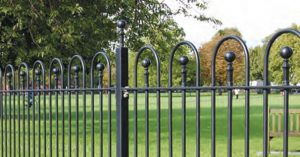 A photo of a vertical bar Bow top railing fence in a park setting