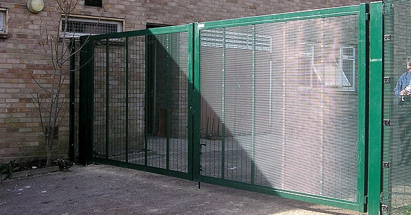 A photo of a green security gate in front of a building