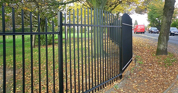 A photo of a vertical bar railing fence in a park setting